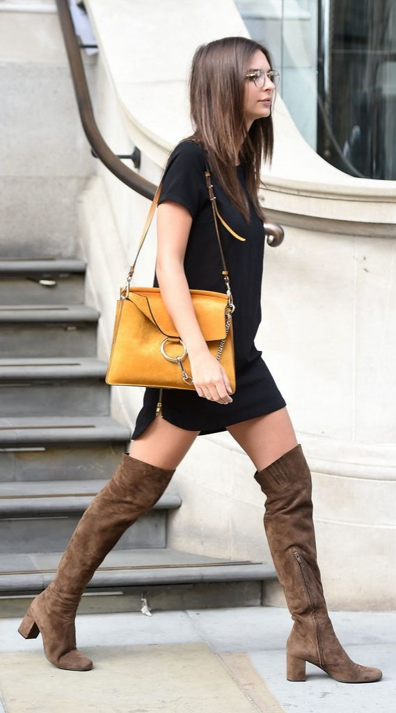 Emily Ratajkowski stepped out in thigh-high suede boots, a bold purse, and a sleep black dress.