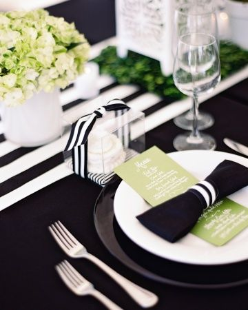 menus are set on the plates along with black napkins folded into the shape of a bow-tie and tied with a ribbon