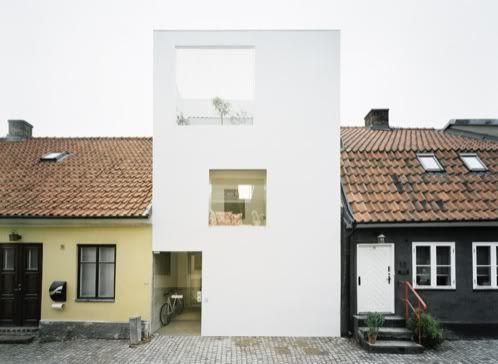 Moderna casa en una parcela de 5m de ancho, sin tabiques, con espacios a doble altura, pasarela y oficina en patio trasero; en una calle con arquitectura antigua.