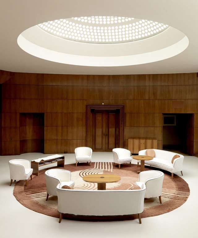 A photograph of the entrance hall at Eltham Palace showing five white art deco chairs positioned around a round brown rug