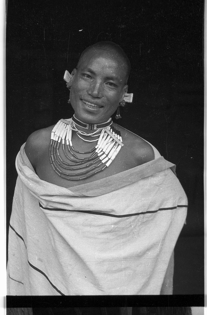 Young man wearing a necklace and ear plugs | par SOAS Digital Library