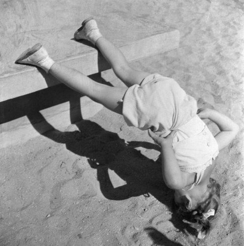 by Eva Besnyö Little girl standing on her head,...