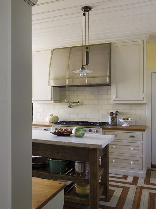 love the freestanding marble topped kitchen island   source: Wendy Posard    Fabulous kitchen with off-white kitchen cabinetry, butcher block counters and brick patterned tile backsplash. stainless steel oven and pot filler faucet. The freestanding marble topped kitchen island holds pots and pans on it's two shelves. A small adjustable vintage style pendant hangs over the kitchen island. The unique hardwood floors are painted and stained to create a geometric pattern.