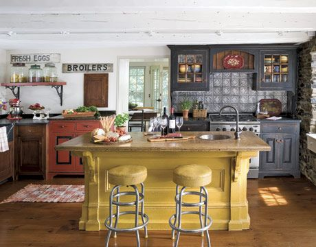 Early American Kitchen  Rich colors and hand-hewn textures define this Early American kitchen. Handcrafted cabinetry hides dinnerware and appliances. Soapstone counters, a tin backsplash, and an antique island complete the look.    Read more: Kitchen Decorating - Ideas for Decorating Your Kitchen - Country Living