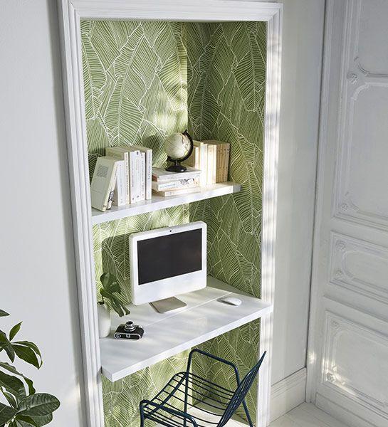 On délimite un espace de travail dans un ancien placard avec un papier peint à motif de feuillage vert bambou.
