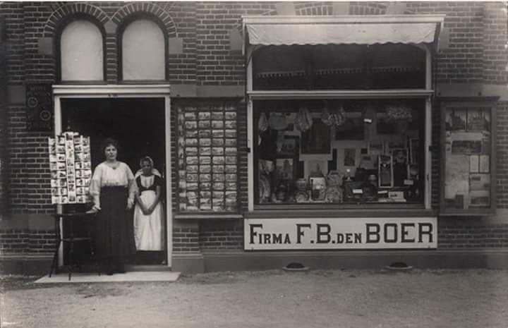 een vrouw en een meisje in de deur van hotel-pension Wilhelmina aan de Noordstraat te Domburg. Met opstelling van de verkoop van ansichtkaarten  Plaats Domburg Datering 1905 - 1915