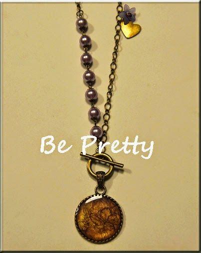Colar comprido, cor cobre, com pérolas de vidro lilás e medalhão pintado à mão, em tons lilás e ouro.