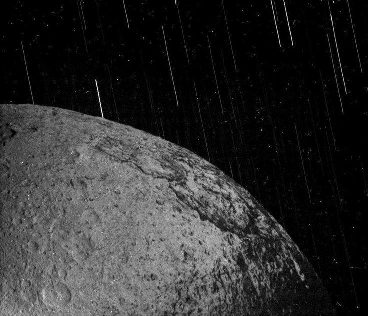 A Storm of Stars - In 2004, Cassini observed Saturn's moon Iapetus. Over the course of about a minute and a half, the camera captured reflected Saturnshine on the night side of Iapetus, and the apparent motion of stars in the background as the moon moved through the sky. The stars appear as streaks; the single dots are noise from radiation hitting the camera sensor.
