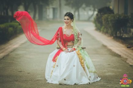 Chitrakshi and Neil   Offbeat wedding in Delhi   Day wedding full of ideas   Indian bride wearing an ivory lehenga with a floral sleeve blouse and a red and pista pastel double dupatta   Indian bride with a red sweetheart blouse with red white and green 3d flower decoupage on the sleeves    Indian bride and groom drinking beer together   photo by Design Aqua   WIttyVows   indoor on the nose