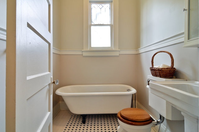 A clawfoot tub in a East Nashville Eastwood Neighbors historic home.  Classic white and not-so-in-character wooden toilet seat.