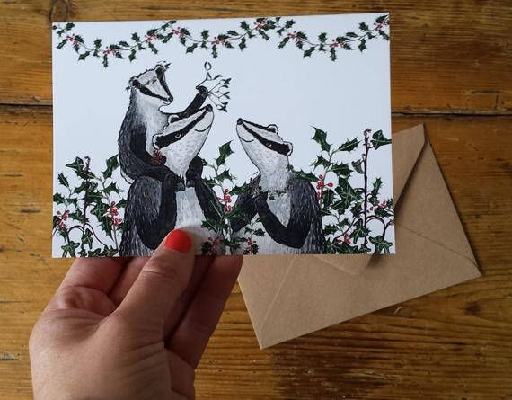 The design originated from Alices new baby / Mothers / Fathers day Badger and Blackberries card. The original drawing is done in pen and watercolour. This family of badgers include festive flora surrounding them - holly and ivy, as well as the little badger holding mistletoe aloft (and a pine cone in the other paw!)  This Christmas Badgers Card is locally printed on FSC card, is A6 (measuring 146mm x 105mm) they are blank inside and come with a brown envelope in a cellophane bag.  T...