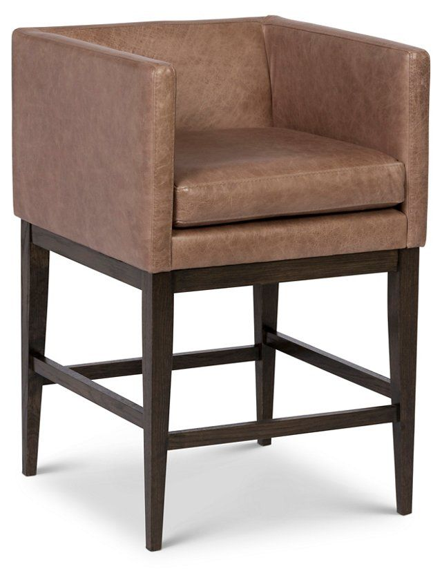 this modern counter stool is elevated on a sturdy hardwood frame with tapered legs and contrasting leather upholstery in a neutral hue