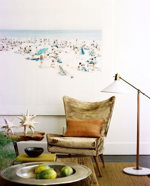 Slick beach art contrasts rich texture in mid-century velvet chair, seagrass/sisal rug, and reclaimed wood coffee table.