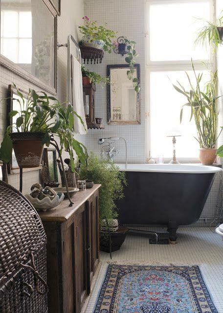 Boho urban jungle badkamer met zwart bad op pootjes en Perzisch tapijt.