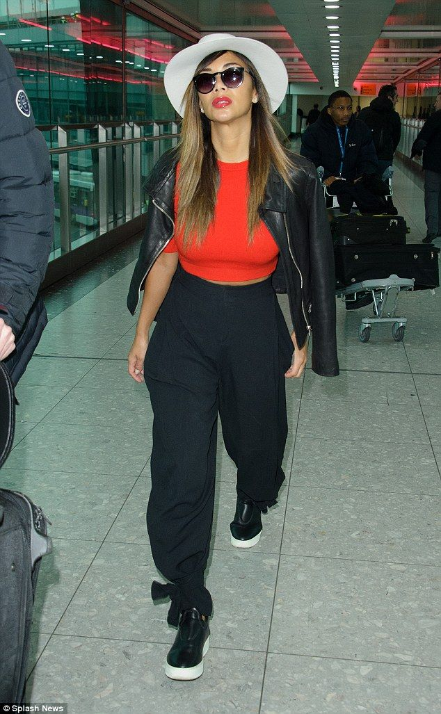Stylish: The Right There hitmaker found the perfect balance between style and comfort for her flight, teaming a pair of loose black tapered trousers with a tight red crop top