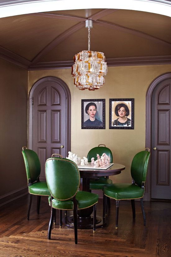 We're nuts about these green leather upholstered chairs paired with the caramel-colored chandelier - Traditional Home®