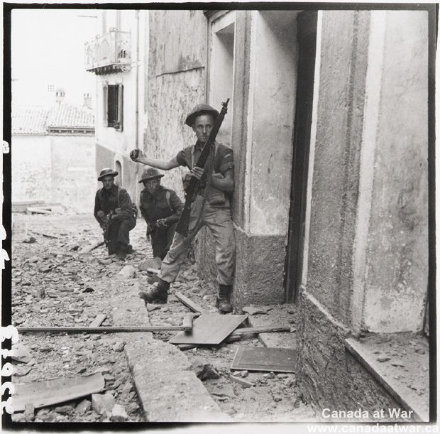 Italy (Misc.) - Three men of the Canadian Infantry Brigade preparing to send a hand grenade into a sniper's hideout in the Maltese Mountains, Campochiaro, Italy, 1943.