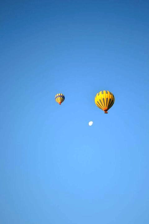 Two hot air balloons and the moon....