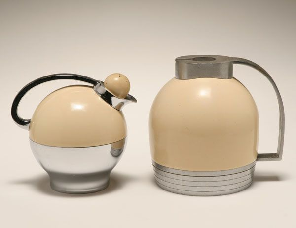 "Two 1930s Art Deco carafe designs for American Thermos Bottle Co. Including a Henry Dreyfuss machine age aluminum model (missing lid), and a chrome ""Spherical Miracle"" form. Both with ivory enamel. Tallest, 7""H."