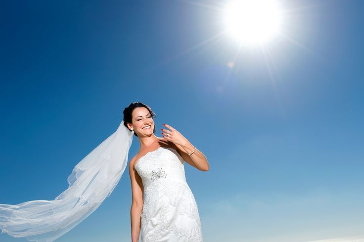 Happy bride veil sun blue sky Greece Santorini wedding planners
