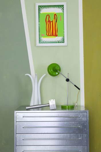 Un'idea da copiare: la cassettiera di zinco – da ufficio o da garage – usata come portadocumenti in soggiorno. Per la parete, una scala di verdi: oliva, menta, smeraldo. Invece delle classiche strisce verticali, trapezi di colore.