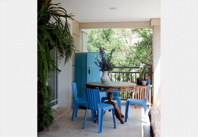 A velha geladeira azul, disposta na varanda, serve para guardar livros. A mesa foi trabalhada pela artista plástica Dedéia Meirelles, dona do apartamento, e as cadeiras Authentics, também azuis, são do designer Matthew Hilton