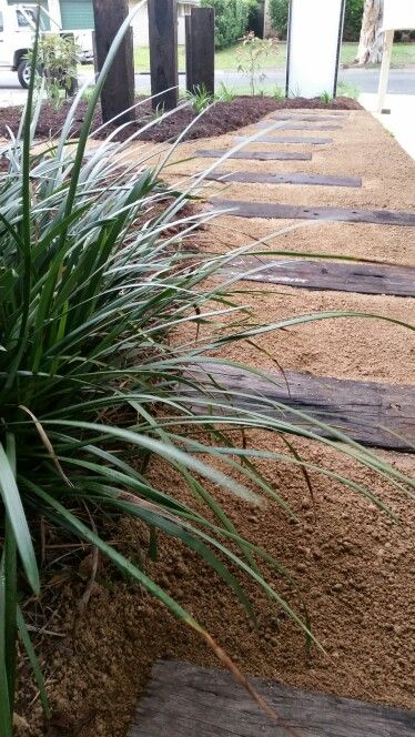 Liriope against a deco and recycled railway sleeper path through native garden.