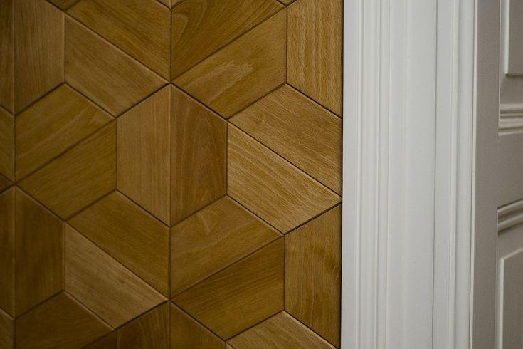 Płytki parkietowe Half-hex ułożone na ścianie w przedpokoju / Half-hex parquet tiles on the hall wall