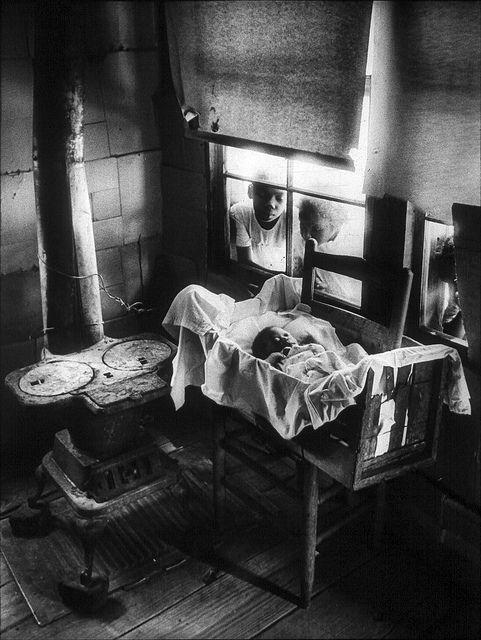 Newborn Baby in Makeshift Crib near Cold Stove, South Carolina, 1951, by W. Eugene Smith