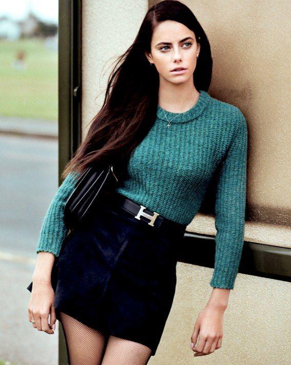 Ella es bonita, alta y delgada. Ella tiene los ojos azules, y pelo castaño que es liso y largo. También, ella lleva un suéter turquesa y una falda negro.