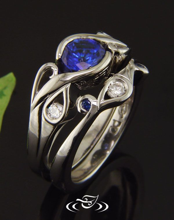 Wonderfully unique and custom Palladium carved calla lily shadow band with Green Lake provided blue sapphires and Alex's family round brilliant cut accent diamond.
