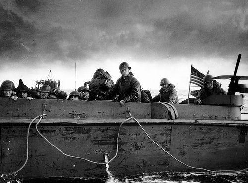 """A bord d'un LCVP, on observe un soldat debout tournant le dos au photographe, qui porte un gilet d'assaut. Le mitrailleur est à son poste à l'arrière du chaland et le pilote a peint son prénom """"JIM"""" sur son casque, le 3ème membre de l'équipage a peint 72 sur son casque ; un radio SCR 300 on voit l'antenne et sur les Cal.30 en défense celle de gauche est équipée d'une boite à munition en bois. #WWII #War"""