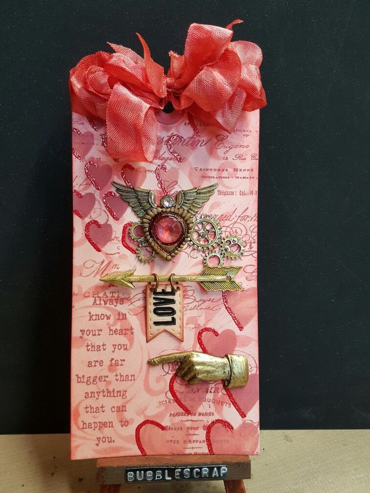 A mixed media tag with distress inks and distress oxides and emerald creek embossing powder