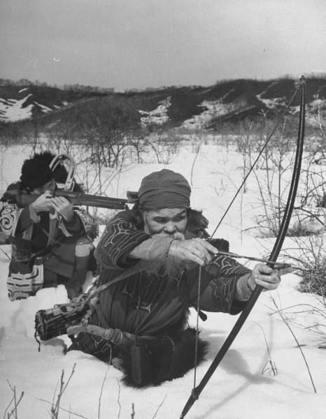Alfred Eisenstaedt,Two Ainu hunters armed with bow and ancient musket, hunting in melting spring snow,Shiraoi, Japan, 1946.
