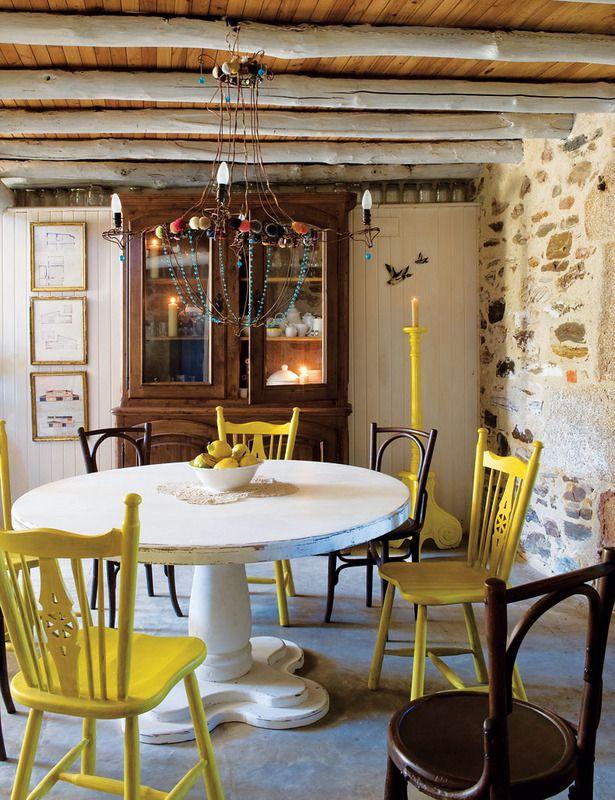 Comedor (Dining Room)  En torno a una mesa pintada de blanco, de Becara, giran unas sillas holandesas pintadas de amarillo y otras antiguas de madera. Lámpara de techo, de Javier Requejo jr., y candelabro de iglesia pintado.