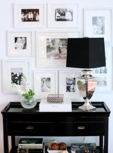 Kerrisdale Design     black & white photo gallery, mirrored lamp with black shade, glossy white lacquer box and Bailey Street glossy black Tamara hall console table.