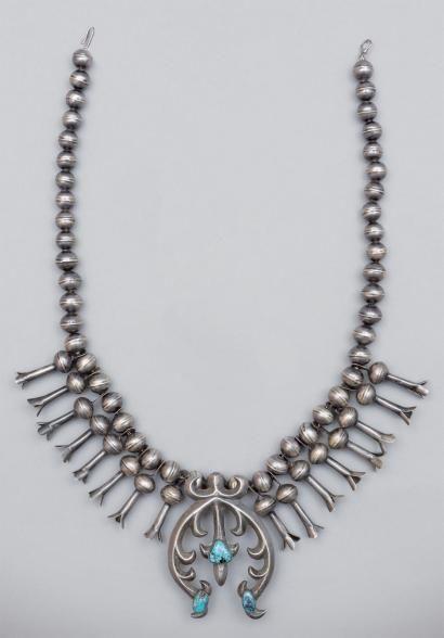 * Collier Navajo Squash Blossom (fleurs de courge). Arizona et Nouveau-Mexique, U.S.A. - ca. 1920-30 Beau collier d'homme Navajo arborant un pendentif (Naja) de style Mauresque (espagnol et Mexicain), ornée de trois turquoises. Le bijou est paré, de chaque côté, de huit pendants en fleurs de courge (Squash Blossom). Argent, chaîne, turquoises.