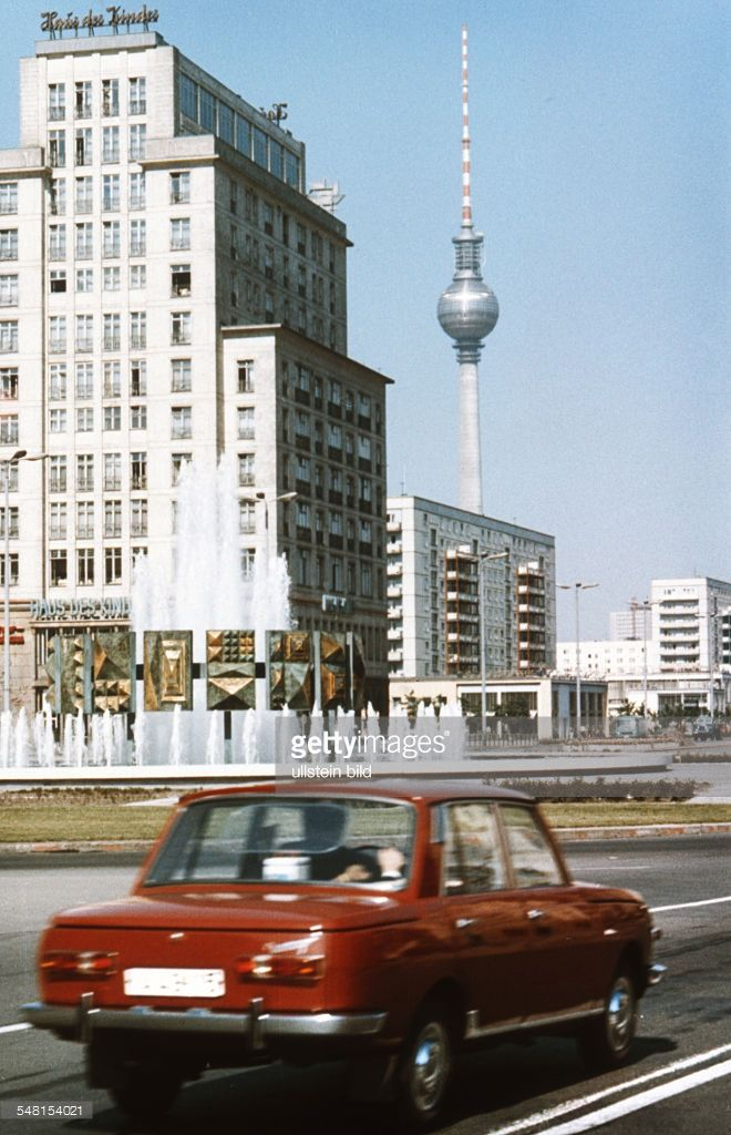 East Berlin - red Wartburg car at the square Strausberger Platz in front of the building Haus des Kindes (house of the child) and the television tower