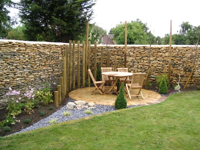 Round corner patio with palisade effect partial enclosure for Small garden plans uk