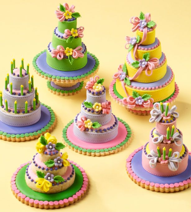 Don't let these mini cakes fool you - they're actually stacks of cookies. Simply topcoated with Royal Icing and then adorned with handmade fondant ribbons and flowers, they steal the show!