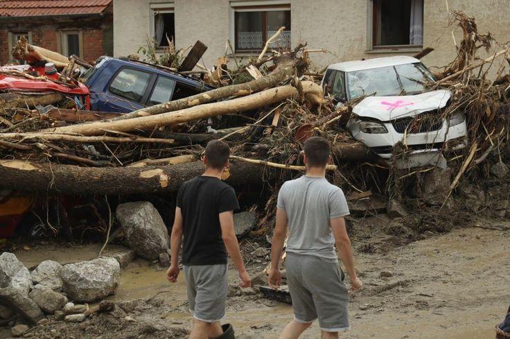 Oamenii trec pe lângă copaci puși la pământ, mașini strivite, case distruse și alte resturi care zac pe o stradă din centrul satului Braunsbach, Germania, în urma unei furtuni puternice și a viiturilor ce au urmat după aceea. Miraculos, potopul din Braunsbach nu a rănit sau ucis pe nimeni, dar în alte zone ale țării furtuna a omorât trei oameni. FOTO Guliver / GettyImages