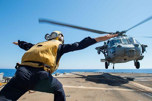 MEDITERRANEAN SEA (July 10, 2017) Personnel Specialist 2nd Class Andre Pangkerego guides an MH-60S Sea Hawk helicopter on the flight deck aboard the guided-missile cruiser USS Philippine Sea (CG 58). The ship is part of the George H.W. Bush Carrier Strike Group, which is conducting naval operations in the U.S. 6th Fleet area of operations in support of U.S. national security interests in Europe and Africa.  (U.S. Navy photo by Mass Communication Specialist 3rd Class Danny Ray Nunez Jr.