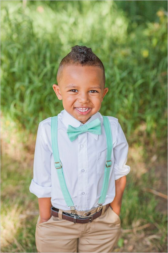 Ring bearer in khaki pants, teal suspenders and bow tie.