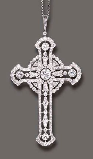 A BELLE EPOQUE DIAMOND CROSS PENDANT NECKLACE  The openwork single and old European-cut diamond cross, enhanced by larger old European-cut diamond collet accents, suspended by a similarly-set bail, to the fine link neckchain, mounted in platinum, (two diamonds deficient), circa 1915, 16½ ins.