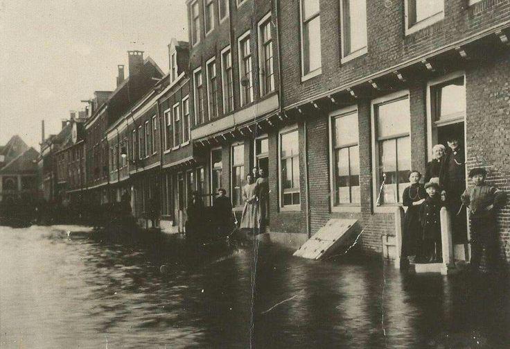 De familie Spruit-de Vries (overgrootouders Tjimpje Meursing) in de deuropening, op de voorgrond, van hun huis aan de Buitenkant tijdens de overstroming in 1916, U kijkt richting de Vischpoortenplas.