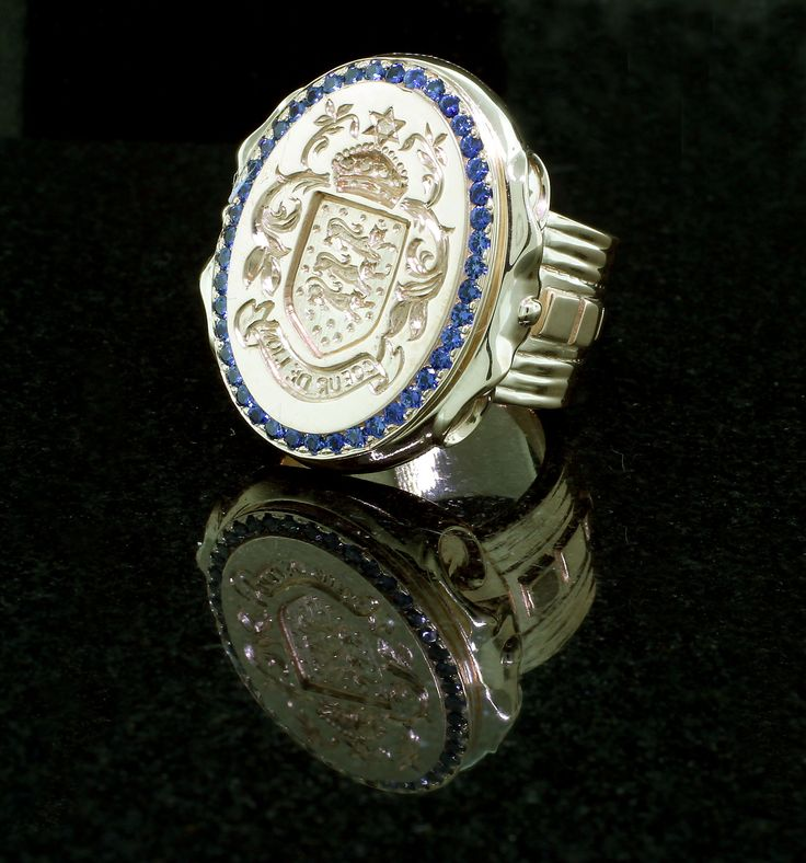 mens handcrafted and custom designed oval insignia ring with blue sapphires, set in 14k yellow.
