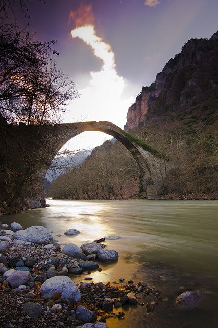 The bridge of Konitsa is the second bigger singe-arched bridge in Epirus, Greece. It was built in 1870. It is located in the entrance of the city at the end of the Aoos canyon. The surrounding scenery is magnificent with the Aoos River flowing under the arch and the bridge with its breathtaking beauty. It is a real piece of art that connects the human culture with the wild nature in a magical way.