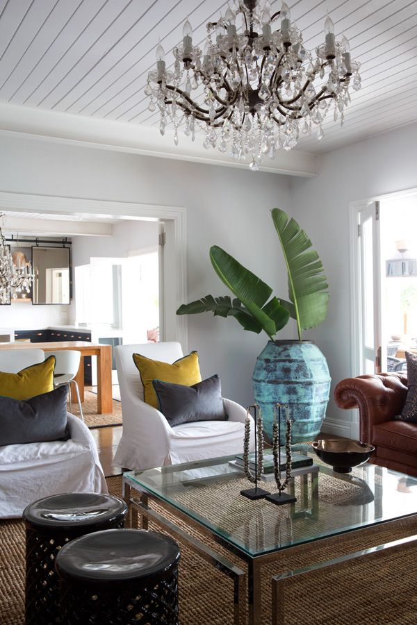 """""""Mod-tropical"""".  Crystal chandeliers add a touch of glamour. The coffee table was custom made by Douglas and Douglas, the occasional chairs are from Weylandts and the rug is from Homestead Decor"""