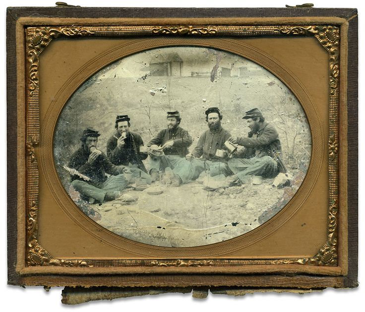 FIVE BUDDIES SIT ON THE GROUND for a classic messmates image. The structures in the background suggest that a permanent camp may be close by, as does the fact these simply dressed Union veterans appear to be enjoying fresh baked bread in place of the ubiquitous hardtack. Now, pass the coffee pot!