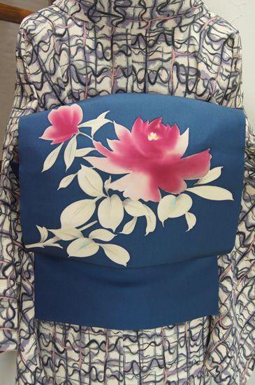 ディープブルーの地に薔薇のような大輪の花模様が美しい正絹塩瀬の名古屋帯です。